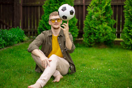 happy smiling young caucasian man with glasses in everyday clothes spins soccer ball on finger on green lawn of country house. football invitation Stockfoto