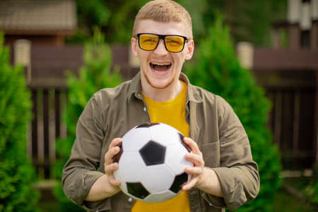 Happy young man holding soccer ball smiling and screaming, laughing football fan support sport team, celebrating victory. People emotions, entertainment concept, successful bet on sports, copy space