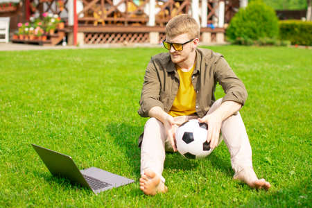 young caucasian man with glasses in everyday clothes posing with soccer ball and laptop sitting on green lawn of country house. distance work, quarantine concept