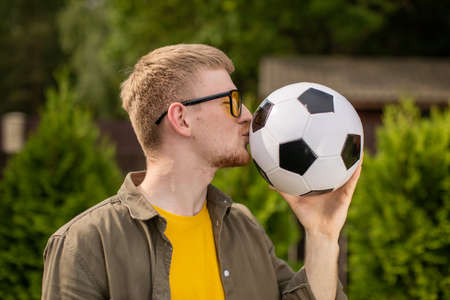 happy smiling young caucasian man with glasses in everyday clothes kissing soccer ball on green background of country house. sporting victories concept, success, goal