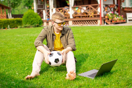 Young handsome man sits on grass near home with soccer ball in hands, male bettor watch sport match online broadcast on laptop, sports betting, bookmakers, football fan have leisure time. Copy space
