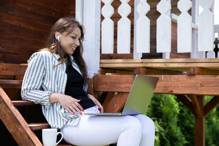 Attractive smiling woman in earphones watching film, young lady working on laptop communicates on internet , study online. Home office outdoors, lifestyle concept, digital, remote work, e-learning Archivio Fotografico