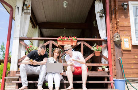 Young positive people discussing business project, startup idea, creative work team work remotely in country house, remote workers sitting outdoors on terrace. Three friends look on laptop screen