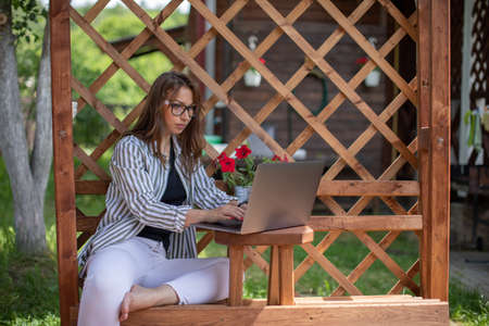 Young attractive businesswoman works remotely using laptop female freelancer sits outdoors at home terrace, smart confident woman surfing net. Modern lifestyle concept, e-learning, digital, copy space Archivio Fotografico