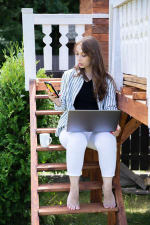 Young woman sitting at yard outdoors, attractive female freelancer working on computer laptop and typing on mobile phone, businesswoman working from home on summer morning. Remote work, lifestyle
