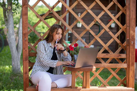 Smart beautiful businesswoman works outside of country house with laptop. Young woman sits in terrace with computer, communicates online, learns remotely. Summer, liberal professions