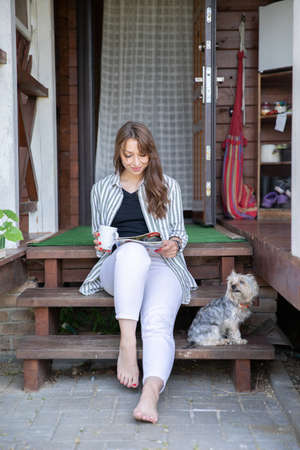 Young beautiful woman resting outdoors with cup of coffee, reading morning press on porch of country house, housewife chilling outside with dog. Summer lifestyle, leisure free time concept. Copy space