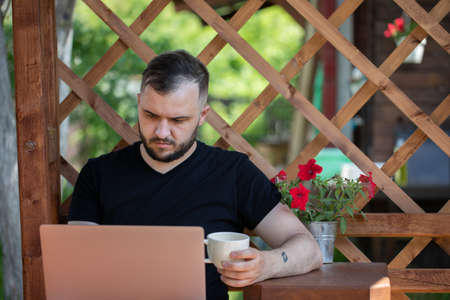 Smart handsome businessman works outside of country house with laptop. Young man sits in terrace with computer, communicates online, learns remotely. Summer, creative professions, freelance concept Archivio Fotografico