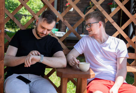 couple of gay men looking at smart watch on background of wooden pergola grid. Relax at countryside summer cottage outdoors. modern gadgets concept. high-speed Internet in cozy farmhouse. Archivio Fotografico