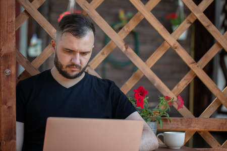 thoughtful bearded Handsome young man wearing black t-shirt looks at laptop on background of wooden pergola grid. distance working concept. Study and work at summer outdoors