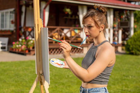 Young beautiful woman female artist painting on easel outside on loan near country house, holding paint brush in mouth, outdoors relaxing activity, creative hobby, creation, inspiration concept