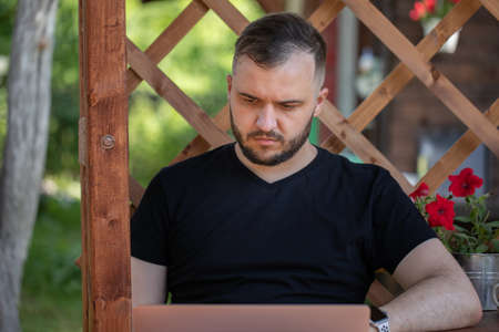 Handsome young man wearing black t-shirt looks at laptop on background of wooden pergola grid. distance working concept. Study and work at summer outdoors. high-speed Internet in cozy farmhouse. Archivio Fotografico