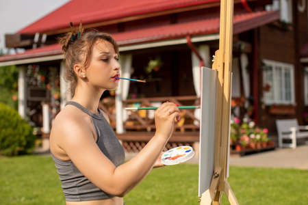 attractive girl paints easel painting holding brush in her teeth outside her country house holding palette of paints in hand. Summer colours concept Creativity concept