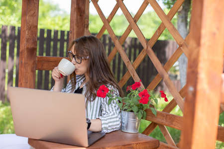 Trendy stylish brunette girl looks at laptop communicating in social network drinking coffee on background of wooden pergola grid. distance working concept. Study and work at summer outdoors