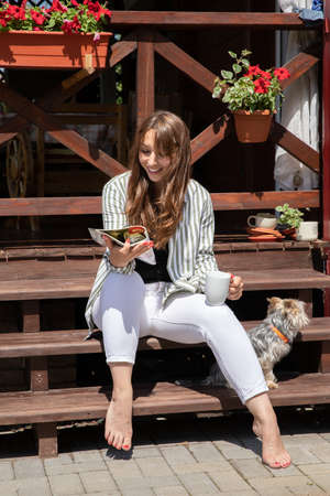 Cool fashionable young woman smiling reading magazine with york dog on wooden cottage terrace. Relax at countryside summer cottage outdoors.