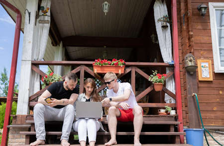 happy young friends Spend time outside with laptop, smartphone, smart watch communicating in social networks. modern gadgets concept. high-speed Internet, communications technology in cozy farmhouse