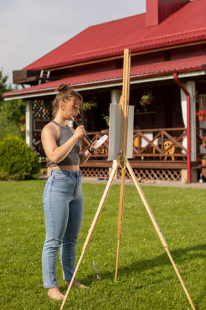 attractive girl paints easel painting at her country house outdoor. Pretty woman is painting. Open air session. Outdoor time for hobbies Archivio Fotografico