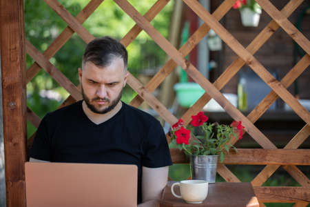 Handsome young man wearing black t-shirt works with laptop on background of wooden pergola grid. distance working concept. Study and work at summer outdoors. high-speed Internet in cozy farmhouse.
