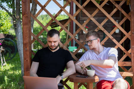 couple of gay men looking at laptop on background of wooden pergola grid. Relax at countryside summer cottage outdoors. high-speed Internet in cozy farmhouse. Archivio Fotografico