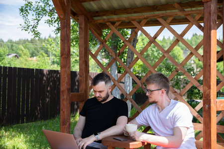 couple of friends looking at laptop on background of wooden pergola grid. distance working concept. Relax at countryside summer cottage outdoors. high-speed Internet in cozy farmhouse.
