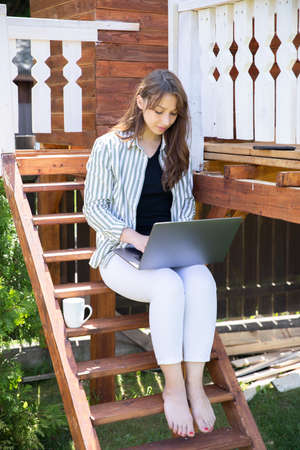 Young smart female freelancer working from home, beautiful woman using laptop, study online outdoors sitting on terrace. Modern concept of freelance, work at home, digital, remote work