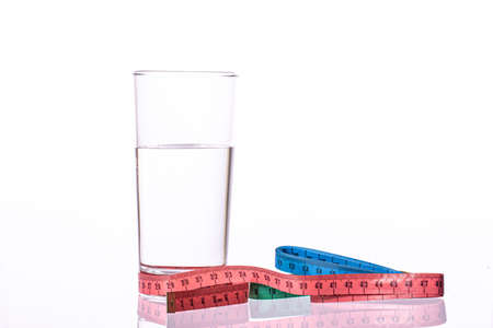 Colorful measuring tapes and glass of water isolated on white background. Diet, sport, healthy eating, weight loss control, healthy lifestyle, drinking balance, nutrition, obesity concept. Copy space