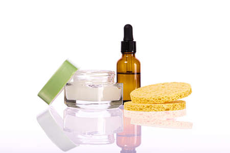 set of cosmetic products for face skin care and rejuvenation. glass brown bottle with pipette and clear transparent liquid, Beige round cosmetic sponge pads. Cosmetic set reflected in glass surface. 免版税图像