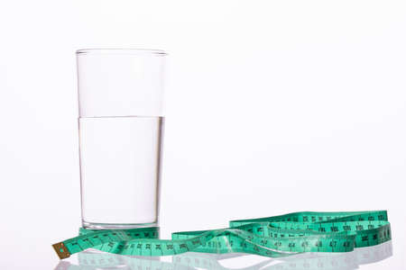Glass of pure natural water tied with green measuring tape isolated on white background. Symbol of diet for loosing weight. Healthy nutrition, abundant drinking during the diet.