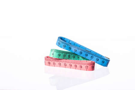 Three colorful measuring tapes isolated on white background. Sewing workshop, clothing repair, fitting, design, tailor workshop. Diet, weight control, healthy lifestyle, body care concept. Copy space Фото со стока