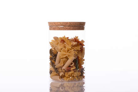 Various raw pasta in transparent jar isolated on white background. Mix of penne, fusilli, farfalle. Italian restaurant, food industry, diet, healthy food, high calorie, recipes concept. Copy space
