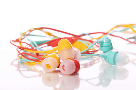 Tangled colorful earphones isolated on white background. Multicolored music accesories, summer playlist, radio podcast, digital music application, cacophony, information noise concept. Copy space