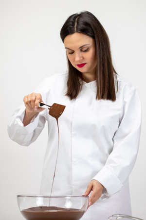 Beautiful female pastry-cook pouring dark melted chocolate isolated on white background. Confectioner making premium hand-crafted chocolate. Candy making, pastry production, bakery, dessert concept