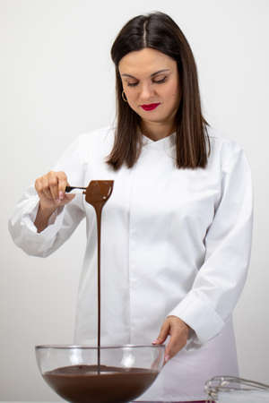 Beautiful female chocolatier pouring dark melted chocolate isolated on white background. Chef make premium hand-crafted chocolate, small-batch chocolate manufacturer, factory, confectionery production