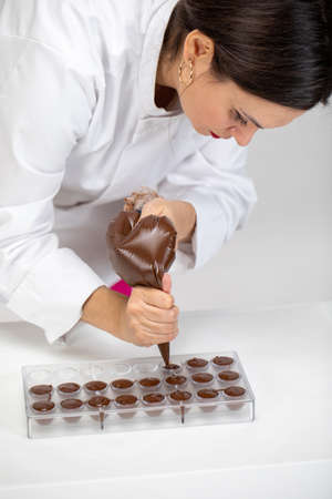 Pretty female chocolatier pouring dark melted chocolate into transparent plastic mold with pastry bag on white background. Confectioner prepare organic hand-crafted chocolate candies. Candy making