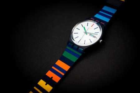 New York, NY, USA 07.10.2020 - Swatch children's swiss made quartz watch isolated on black background. colored plastic case striped design, day and date Thursday 22, youth hipster style watch for bright image. 版權商用圖片