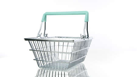 Empty metal shopping basket with handles in action rotating on isolated white background. Store, supermarket, e-commerce, online shopping, special offer, black friday sale concept. Copy space Archivio Fotografico