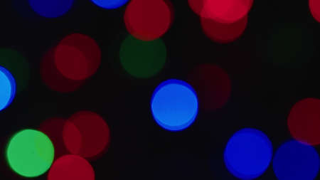 New year or Christmas shimmering festive garland blurred backdrop in Deep blurring and focusing. Quick flickering multicolored lights abstract background. defocused Glitter light spots on dark.