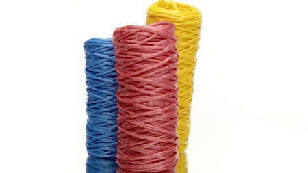 Three skeins of colorful recycled plastic twine rotating on isolated white background. Hank of nylon rope knot strings in motion. Eco-friendly materials, ecology concept. Copy space
