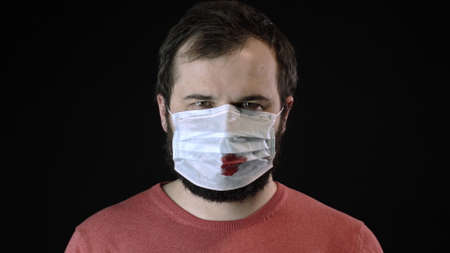 Sick man in medical mask with blood on it puts on one more new mask. Global spread of coronavirus pandemic. Concealment of disease. Protection of infection covid-19. Lockdown. Quarantine concept