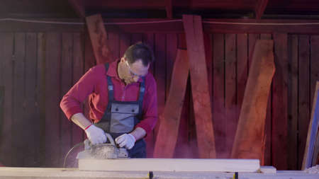 Man carpenter cleans the surface of wooden beam using electric planer in workshop and flies sawdust. Work with electric planer for polish boards and bar. DIY furniture manufacturing concept.