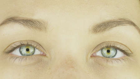 Expressive sincere cheerful female green eyes of young girl, with yellow center without makeup, open, joyful looking directly at the camera, blinking, smiling. Close-up. Vision correction concept