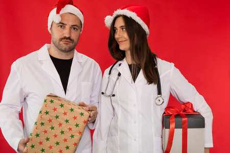two doctors man and woman in Santa Claus hats hold Christmas gift boxes looking at camera. Advice on right healthy lifestyle on holidays. Gift delivery to work