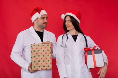 two doctors man and woman in Santa Claus hats hold Christmas gift boxes looking at each other. Merry Christmas and Happy New Year for healthcare professionals. Gift delivery to work