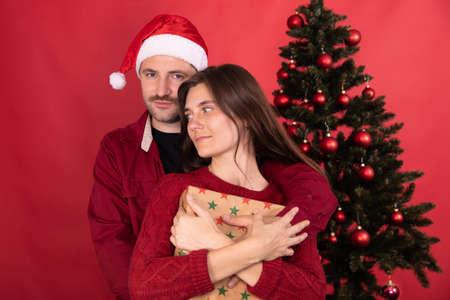 romantic couple of lovers dressed casually with gift is gently hugging on background of Christmas tree in red studio.