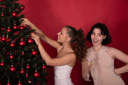 couple of two attractive young girls joyfully decorate Christmas tree drinking champagne looking at camera on studio red backdrop. Happy loving partners enjoying in Christmas