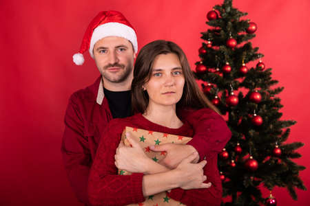 Lovely cute couple posing at home infront of xmas tree, celebrating New Year, man in santa hat and young woman with Christmas gift on red background. Winter family holidays concept, copy space