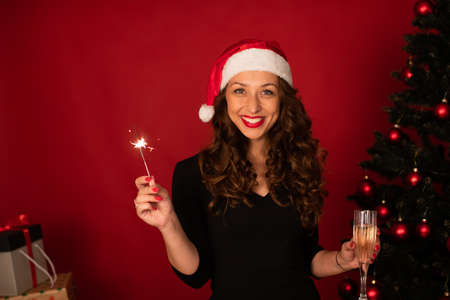 Beautiful long-hair brunette girl in Santa Claus hat sends Christmas greetings to her loved ones by zoom celebrating New Years Eve alone. Christmas tree on studio red backdrop copy space Festive mood Archivio Fotografico