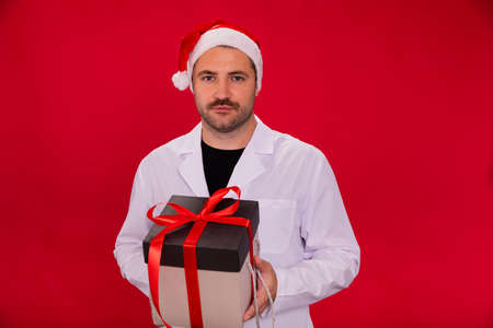 Unshaven tired doctor in Santa Claus hat holds Christmas gift box looking at camera isolated on red studio background copy space. Merry Christmas and Happy New Year for healthcare professionals