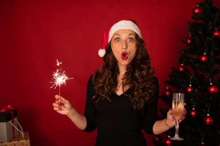 Surprised face Beautiful long-hair self-gifter girl in Santa Claus hat excited screaming celebrates Christmas or New Year alone with Burning sparklers and champagne. Christmas tree on studio backdrop