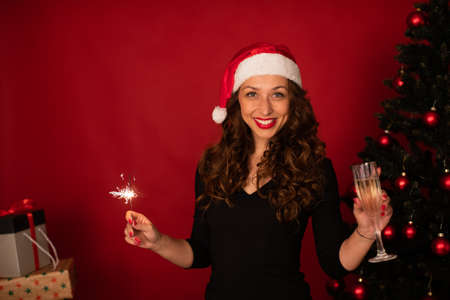 Layout for New Years corporate Christmas greetings or invitations copy space. Beautiful long-hair brunette girl in Santa Claus hat smiling looks at camera with Burning sparklers and champagne in hand